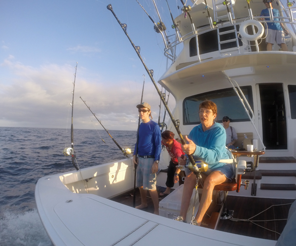 Debbie Conway reels in an early morning wahoo at the Flower Garden Banks on Feb. 9, 2015. David Weiss Jr. waits with the gaff, deckhand Tatum Frey clears the cockpit while Ron McDowell observes the fight and Capt. Billy Wright maneuvers the boat.