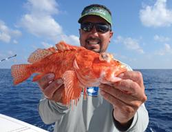 Josh Graves carefully holds up a scorpionfish.